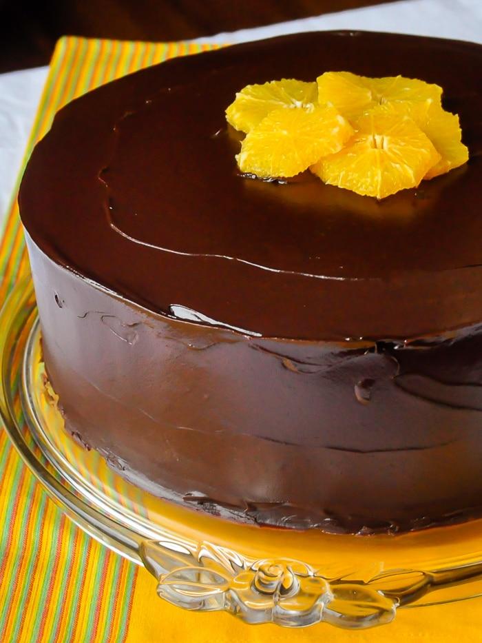 Chocolate Orange Cheesecake Layer Cake photo of uncut cake on a glass cake plate