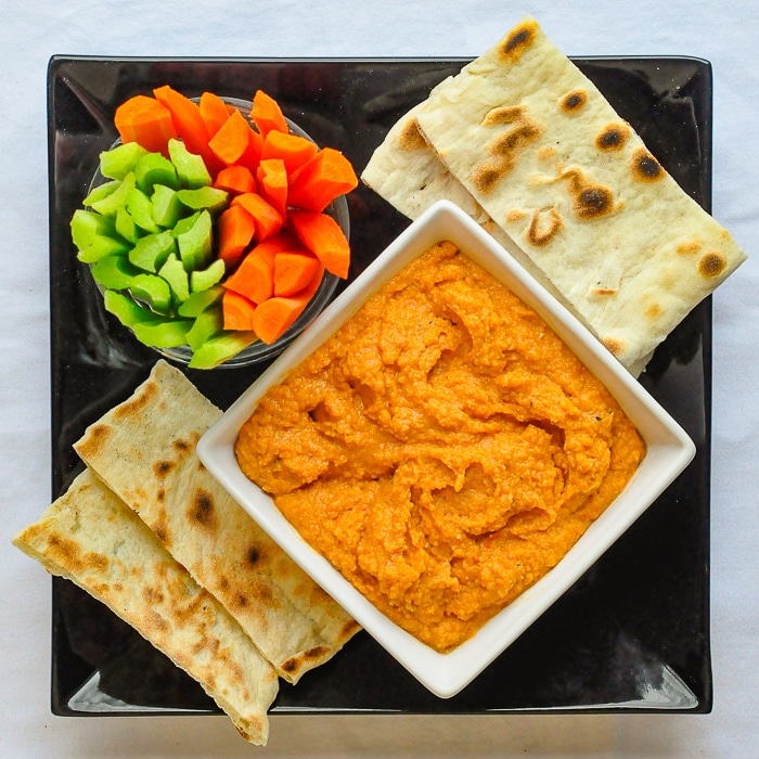 Roasted Red Pepper Hummus in a white bowl with veggies and flatbread