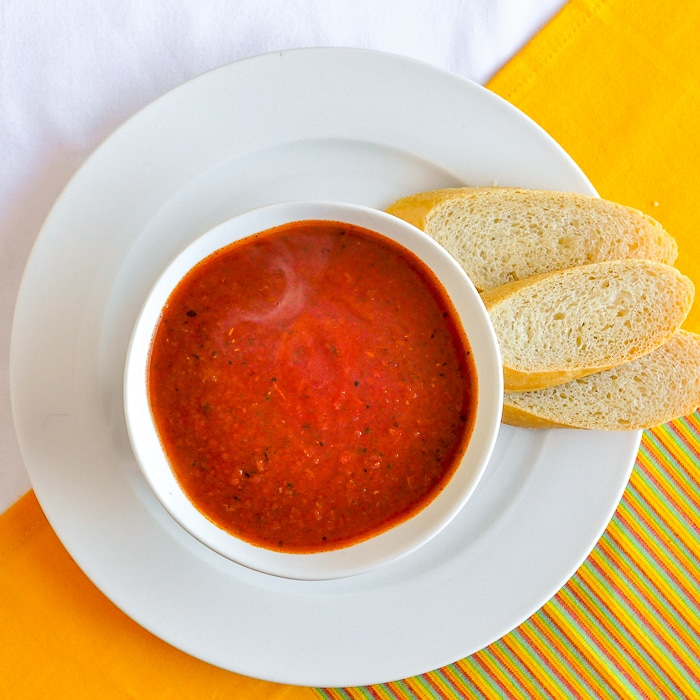 Roasted Tomato Fennel Soup wide shot of a serving in white bowl with baguette on the side