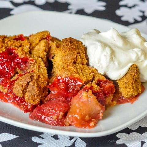Strawberry Apple Graham Crumble close up image on a white plate with whipped cream