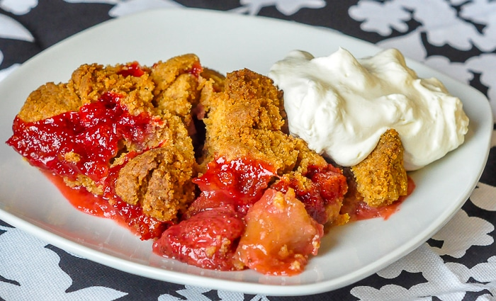 Strawberry Apple Graham Crumble wide image of full serving on a white plate with whipped cream