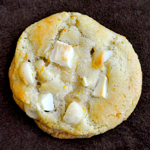 White Chocolate Orange Macadamia Cookies photo of one cookie on a brown background