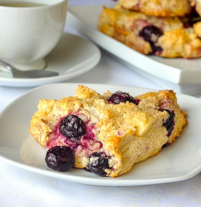 Cherry Cheesecake Scones. Single scone on plate with cup of tea and platter of scones in background