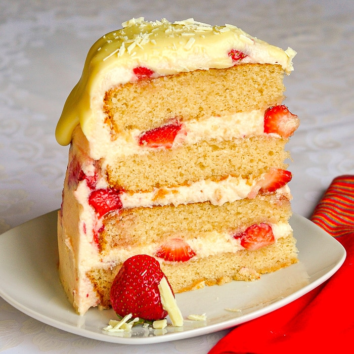 Strawberry White Chocolate Buttercream Cake photo of a single slice of cake on a white plate