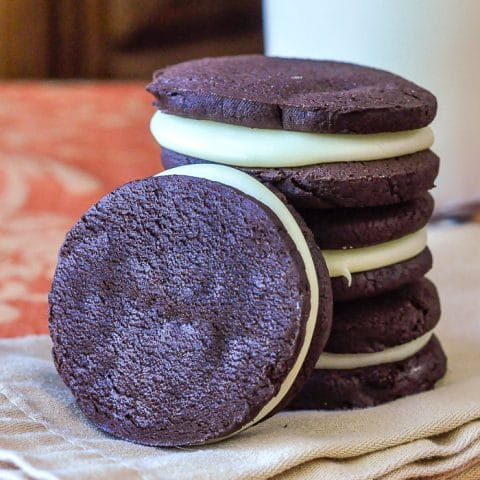 Homemade White Chocolate Fudge Oreos photo stacked on a napkin with milk in the background