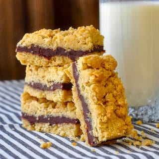 Nutella Fudge Crumble Bars shown stacked with a glass of milk