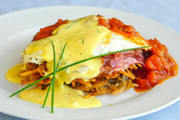 omato Eggs Benedict with Potato Latkes and Prosciutto wide image showing full serving on a white plate