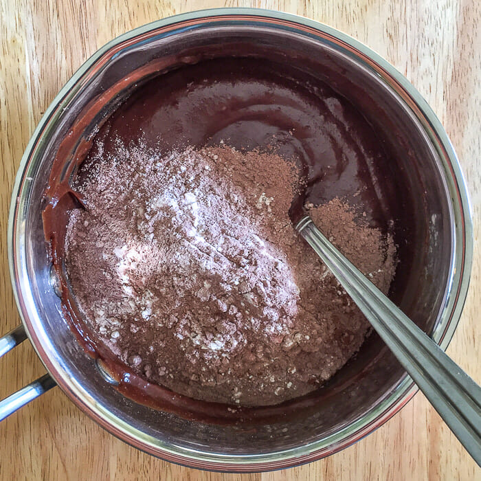 Adding the dry ingredients to brownie batter.