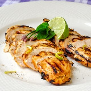 Chili Lime Cumin Grilled Chicken close up photo on white plate with lime wedge