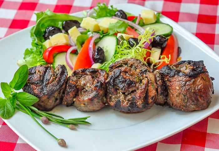 Herb and Garlic Rolled Steak Medallions wide photo on serving plate.