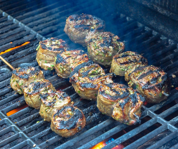 Herb and Garlic Rolled Steak Medallions grilled to perfection on an outdoor gas grill.