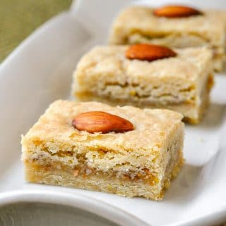 Orange Almond Cookie Bars close up image of a cookie square on rectangular white serving platter.