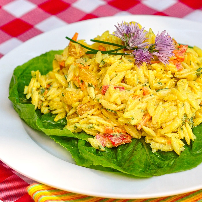 Creamy Curry Orzo Salad on a bed of lettuce on a white plate