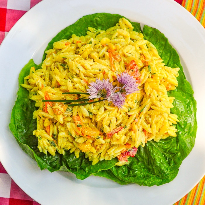 Overhead shot of Creamy Curry Orzo Salad on a bed of lettuce