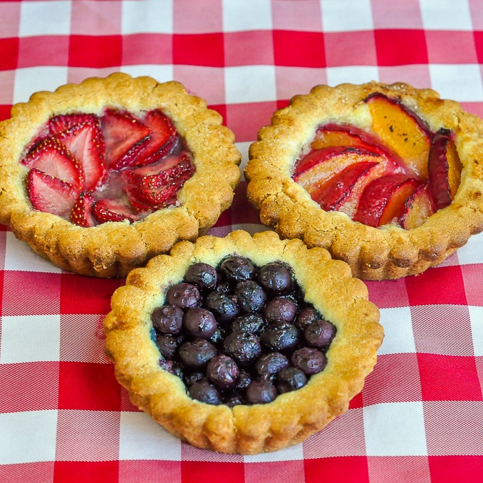 Summer Fruit Cookie Tarts shown on a red checkered table cloth
