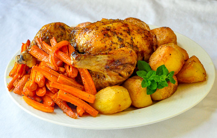 Glazed Maple Chipotle Roast Chicken with roasted vegetables on a white serving platter