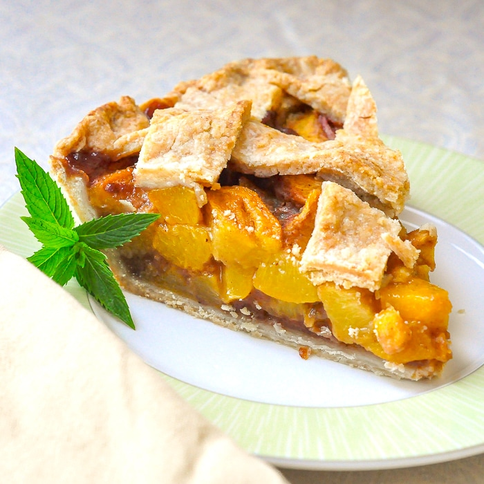 One slice of peach pie on a green an white plate