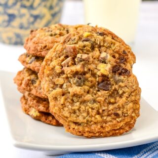 Chocolate Pecan Crunch Cookies stacked on a white plate with a glass of milk in the background