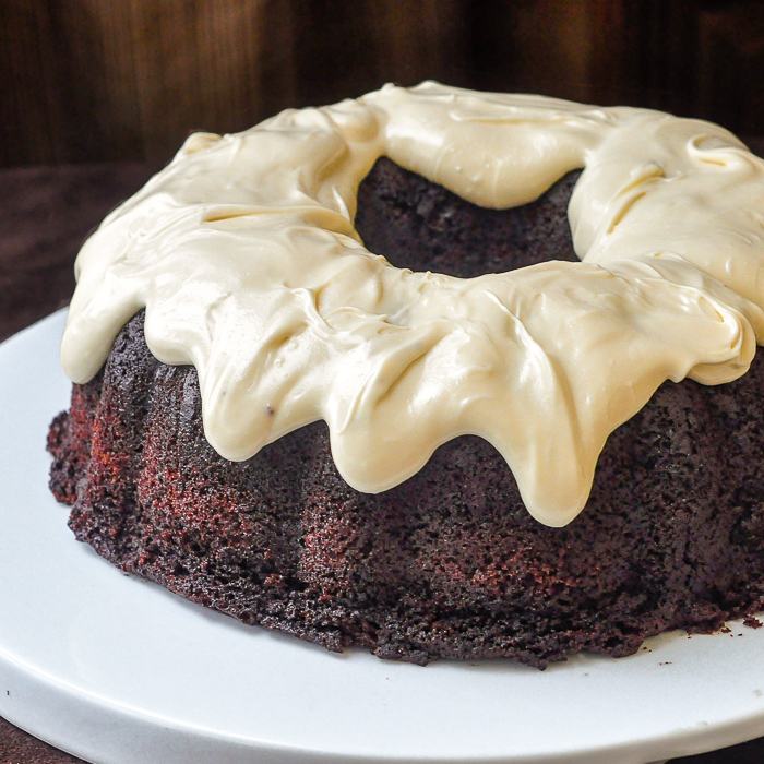 Chocolate Zucchini Cake with Cream Cheese Glaze photo of uncut cake on a white plate