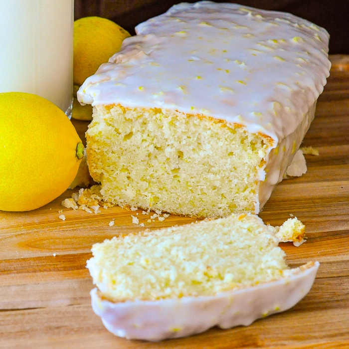 Glazed Lemon Pound Cake on a wooden cutting boards with lemons and a glass of milk on the side