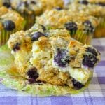 Blueberry Oatmeal Lemon Cheesecake Muffins close up shot of a muffins split open to reveal the cheesecake centre