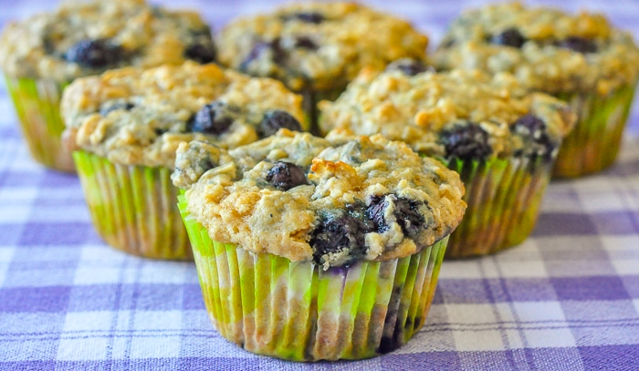 Blueberry Oatmeal Lemon Cheesecake Muffins wide shot of 6 muffins on a blue checkered table cloth