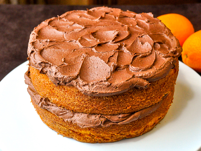 Photo of uncut Orange Velvet Cake on a white serving platter