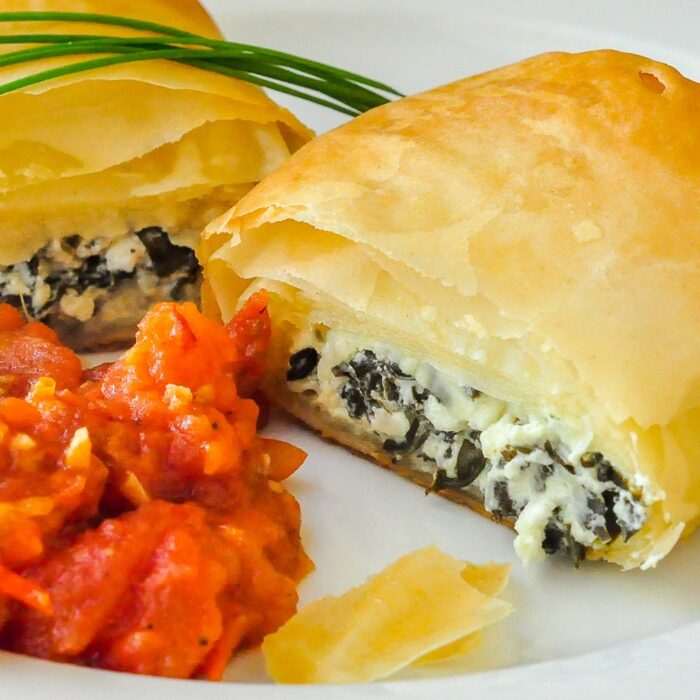 https://www.rockrecipes.com/wp-content/uploads/2012/10/Goat-Cheese-Spanakopita-Rolls-close-up-shot-of-single-roll-with-tomato-compote-on-a-white-plate.jpg