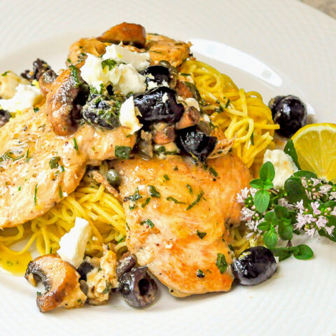Mediterranean Lemon Butter Chicken close up photo of a single serving on a white plate