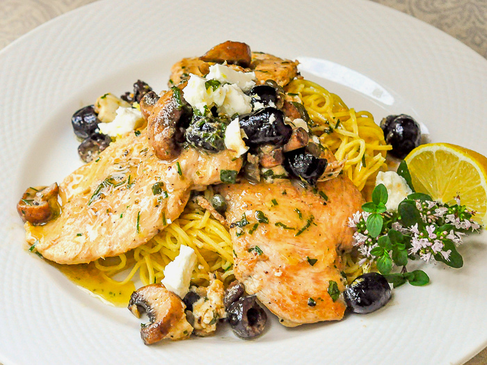 Mediterranean Lemon Butter Chicken pictured with oregano flowers and lemon wedge on a white plate