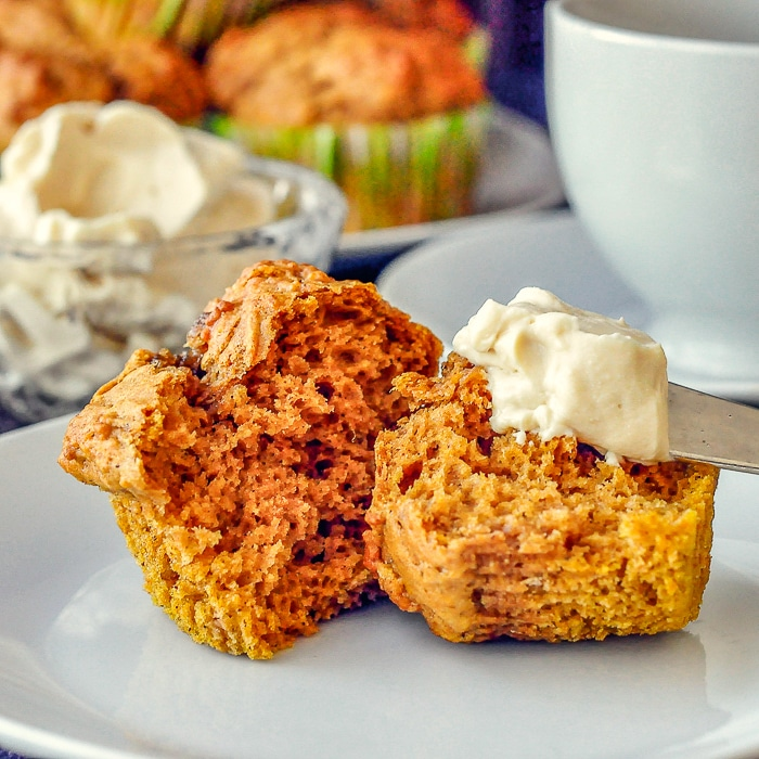 Pumpkin Spice Muffins photo of single muffin with knife smearing on maple cream cheese