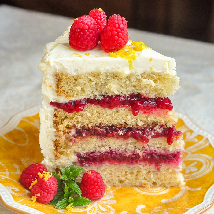 Raspberry Lemon Buttercream Cake photo of a single slice on a yellow plate showing all four layers