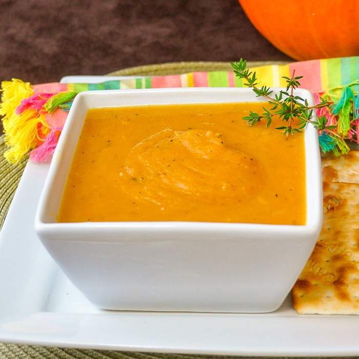 Roasted Pumpkin Soup in square white bowl with crackers on the side