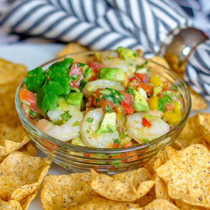 Avocado Lime Shrimp Salsa close up image in glass bowl surrounded by tortilla chips