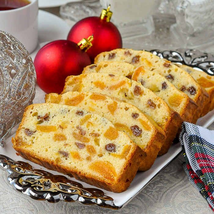 Aprivot raisin cake on a white and silver platter with red Christmas tree decorations.