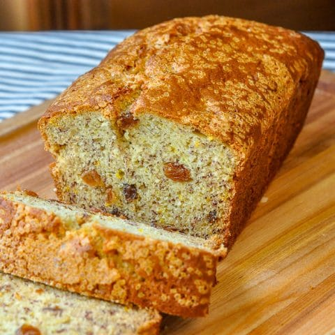 Orange Raisin Five Spice Banana Bread photo of cut loaf on a wooden cutting board