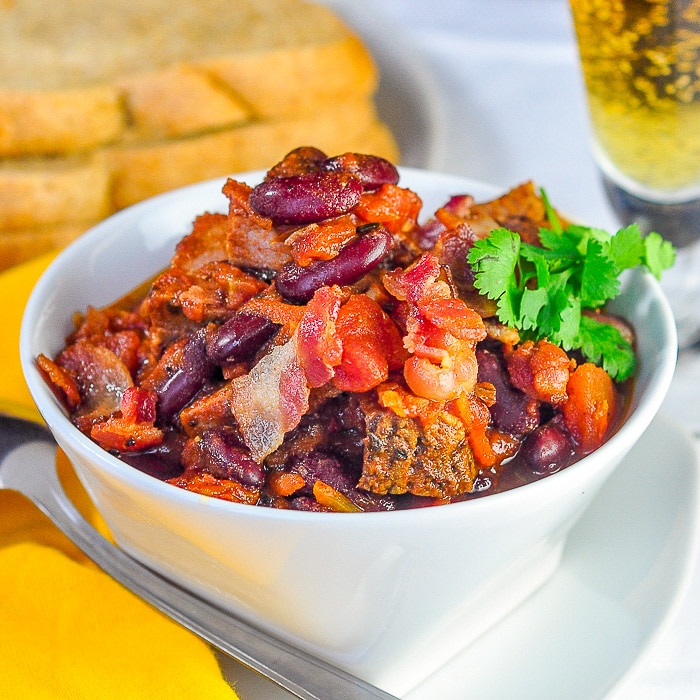 Prime Rib Beer BAcon Chili square cropped featured image of chili in a white bowl with crispy bacon garnish