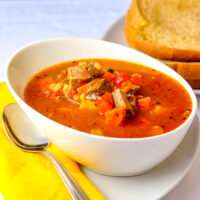 Braised Beef Tomato Barley Soup in a white bowl
