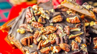 Chocolate Toffee Pecan Brittle pictured on a red plate with Christmas decorations in the background.