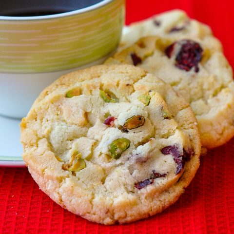 Pistachio White Chocolate Cranberry Cookies close up photograph of cookies with a cup of coffee on red background