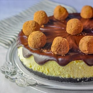 Rum Truffle Cheesecake shown on a clear glass serving plate