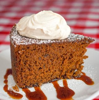 Triple Ginger Gingerbread Cake photo of a single slice topped by thick cream