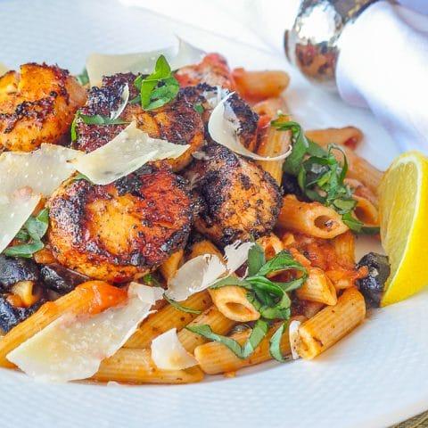 Cajun Scallops Puttanesca close up photo of a single serving on a white plate
