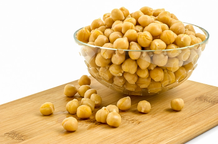 Washed and drained canned chick peas in glass dish on bamboo board isolated on white background. Stock Photo
