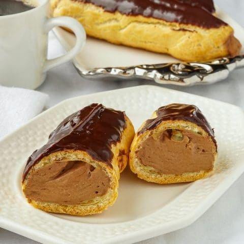 Chocolate Mousse Eclairs photo of one eclair cut open to reveal filling