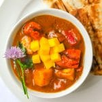 Easy Mango Chicken Curry close up photo of single serving in white bowl with Naan on the side