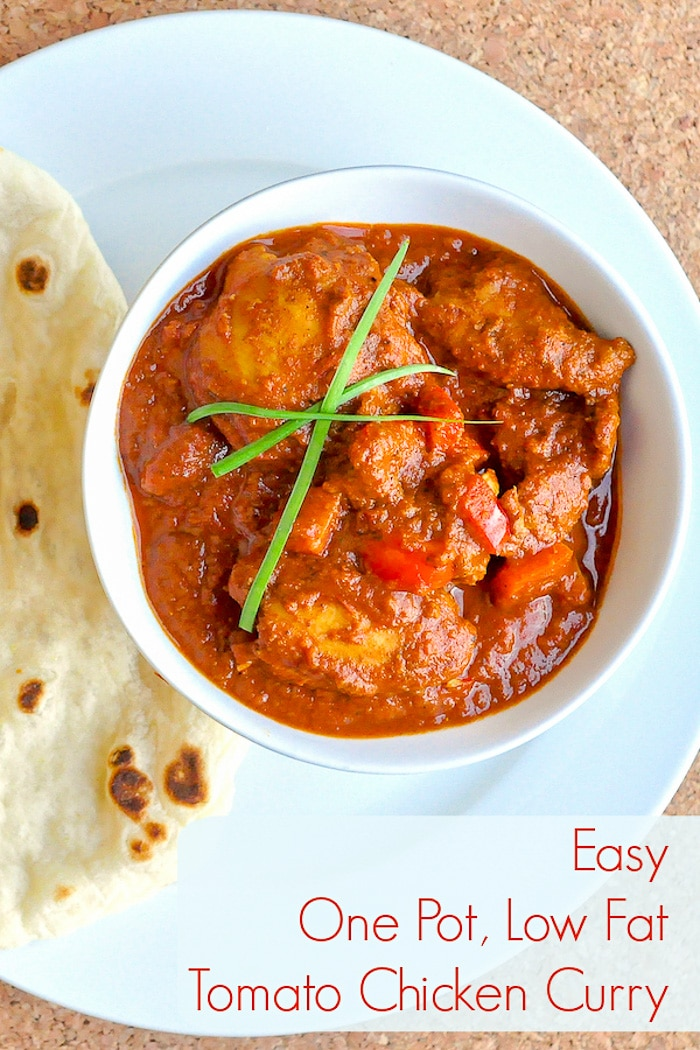 Easy One Pot Low Fat Tomato Chicken Curry close up pgoto of single serving in a white bowl with naan on the side.