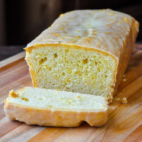 Glazed Orange Pound Cake on a wooden cutting board with one slice cut off