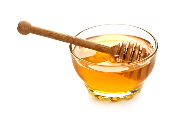 Honey in a glass pot with a solid white background.