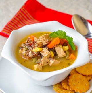 Lemon Chicken Soup with red quinoa and thyme shoyn in a white bowl with crackers on the side.